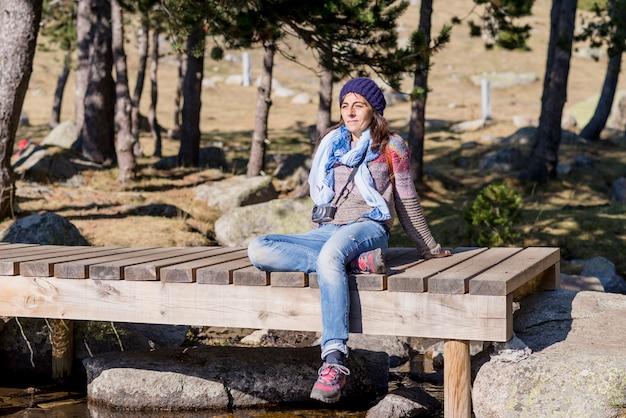 Frau in der wollmütze, die auf einer hölzernen brücke über einem strom beim sonnenbaden in einem wald sitzt