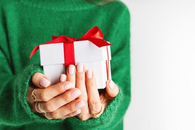Frau in der woolen grünen strickjacke, die eine anwesende rote geschenkbox mit einem bogen hält. weihnachtsfestliches layout. modell für das neue jahr. breites banner.