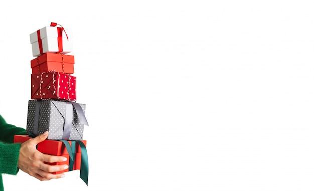 Frau in der woolen grünen strickjackenholding stellt verschiedene farbige geschenkboxen auf weißem hintergrund dar. weihnachtsfestliches layout. modell für das neue jahr. breites banner.