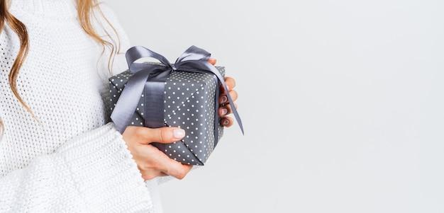 Frau in der woolen weißen strickjacke, die eine geschenkbox mit einem bogen hält. weihnachtsfestliches layout. modell für das neue jahr. breites banner.