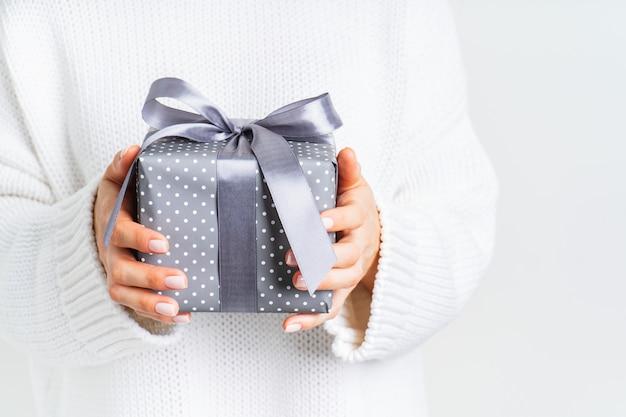 Frau in der woolen weißen strickjacke, die eine geschenkbox mit einem bogen hält. weihnachtsfestliches layout. modell für das neue jahr.