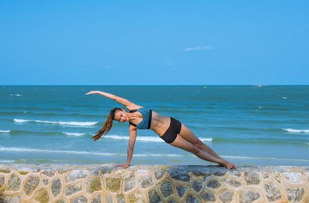 Frau in der yogahaltung am strand, am yogarückzug und am training.