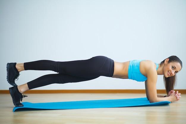 Frau in der yogaklasse, die aufwärtsgerichtete hundehaltung macht