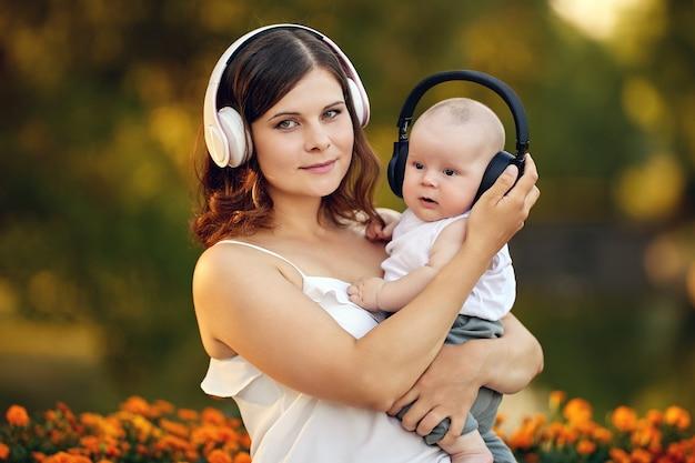 Frau in drahtlosen kopfhörern mit kleinem jungen geht auf natur