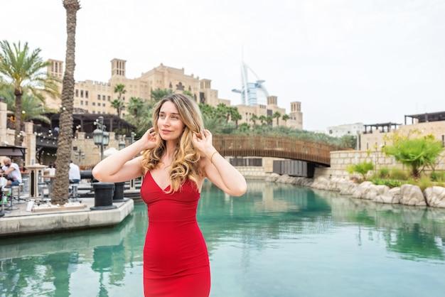 Frau in dubai, vereinigte arabische emirate. attraktive dame, die ein rotes kleid trägt. mädchen, welches die stadtansichten bewundert