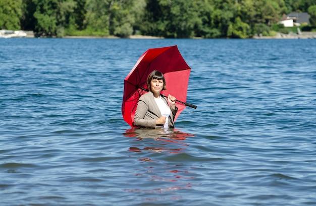 Frau in einem anzug, der einen roten regenschirm hält, der in der mitte eines sees steht