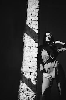 Frau in einem anzug durch die backsteinmauer
