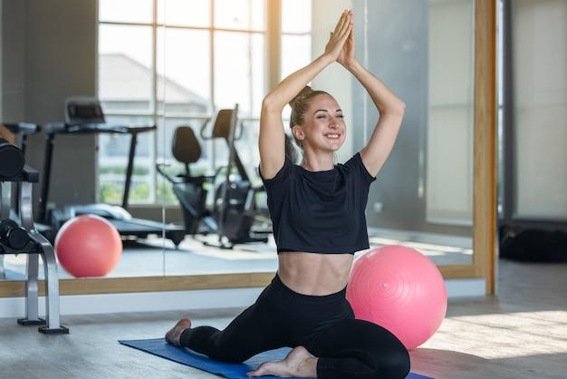 Frau in einem athletischen look mit aerobic-übungen, die sich locker ausdehnen, junge sportliche frau, die sich in lotus-pose ausdehnt, macht yoga-übungen, atmet frische luft und meditiert im fitnessstudio mit sonnenlicht im fitnessstudio.