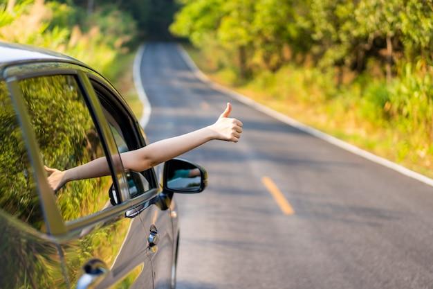 Frau in einem auto, das ein zeichen tut