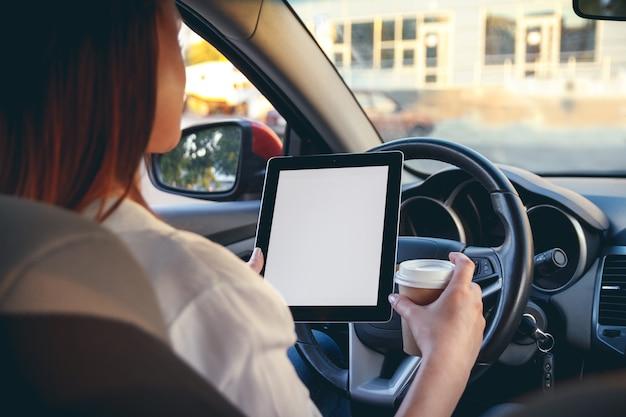 Frau in einem auto mit einer tablette in den händen