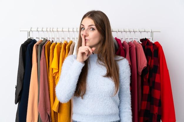 Frau in einem bekleidungsgeschäft mit vielen kleidern hinten