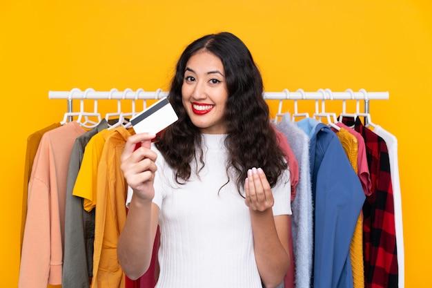 Frau in einem bekleidungsgeschäft und im besitz einer kreditkarte