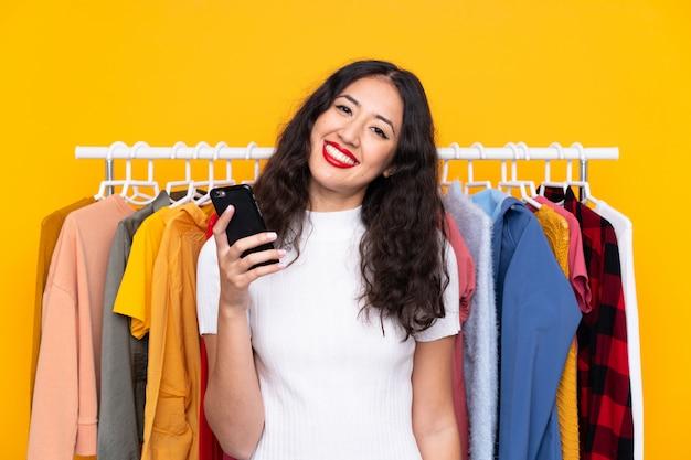 Frau in einem bekleidungsgeschäft und im gespräch mit mobile