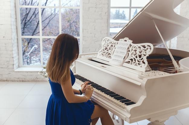 Frau in einem blauen abendkleid, das auf einem weißen klavier spielt