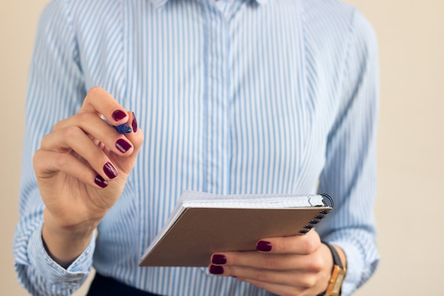 Frau in einem blauen gestreiften hemdschreiben in einem notizbuch