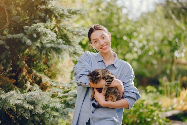 Frau in einem blauen hemd, das mit niedlichem kätzchen spielt