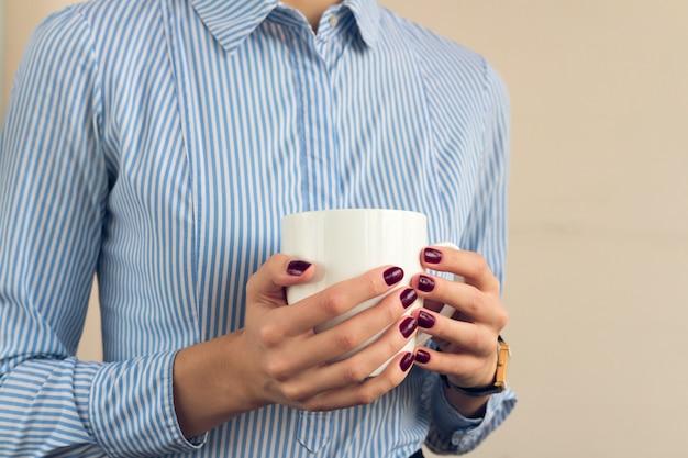 Frau in einem blauen hemd und in einer roten maniküre, die eine weiße schale mit zwei händen nah hochhalten