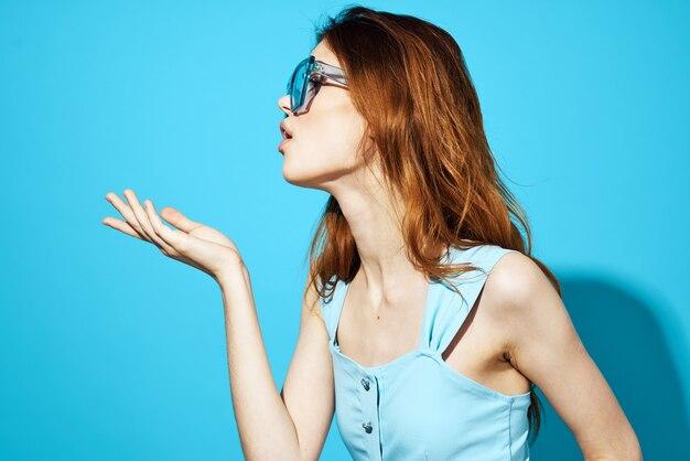 Frau in einem blauen kleid, das studiospaßmodell aufwirft