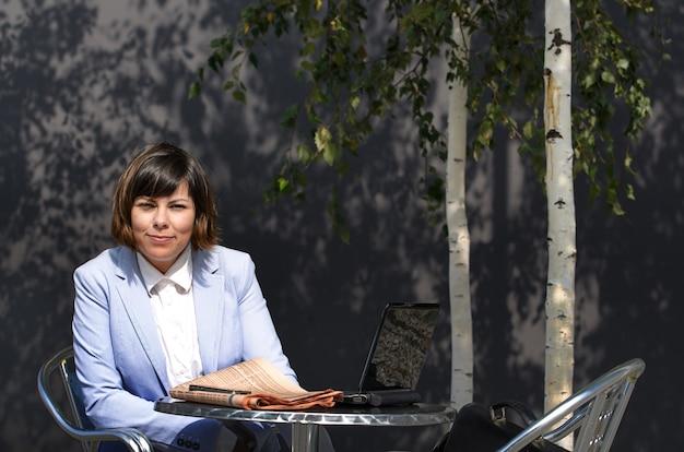 Frau in einem blauen mantel, der auf einem tisch mit einem laptop nahe den bäumen im hof steht
