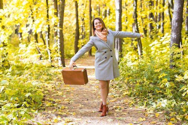 Frau in einem blauen mantel, der im herbstpark mit koffer tanzt