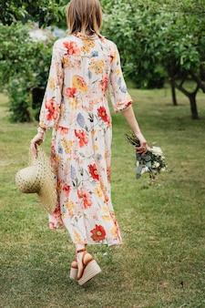 Frau in einem blumenkleid spaziert in einem garten