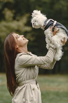 Frau in einem braunen mantel. dame mit einem labrador