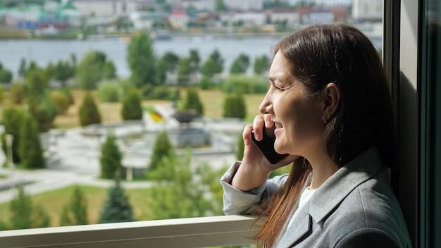 Frau in einem business-anzug telefoniert am offenen fenster vor dem hintergrund eines grünen parks