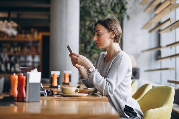 Frau in einem café, das zu mittag isst und am telefon spricht