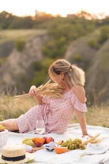 Frau in einem eleganten kleid, das ein picknick hat
