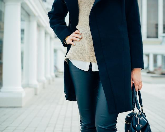Frau in einem eleganten mantel, der eine handtasche in einer hand, die andere hand auf ihrer taille hält