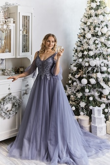 Frau in einem festlichen kleid steht in der nähe des weihnachtsbaumes