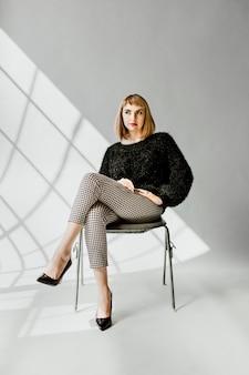 Frau in einem flauschigen pullover sitzend