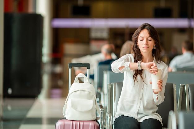 Frau in einem flughafenaufenthaltsraum, der auf flug wartet. kaukasischer tourist, der nach zeit im warteraum sucht