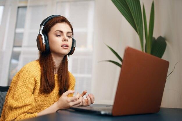 Frau in einem gelben pullover vor einem laptop zu hause arbeitet freiberuflich