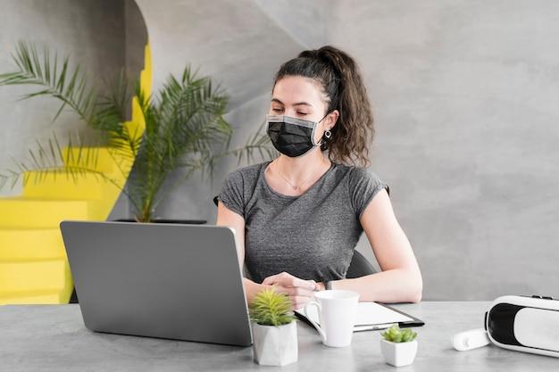Frau in einem geschäftsbüro, das medizinische maske trägt