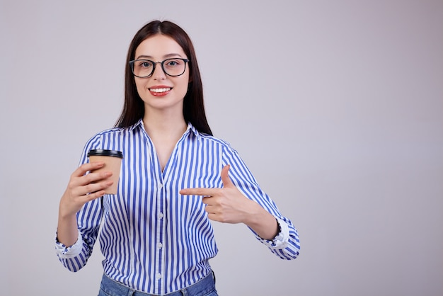 Frau in einem gestreiften hemd und einer schwarzen pc-brille steht mit einer braunen tasse kaffee in der hand auf grau. die dame schaut ruhig geradeaus. lächeln.