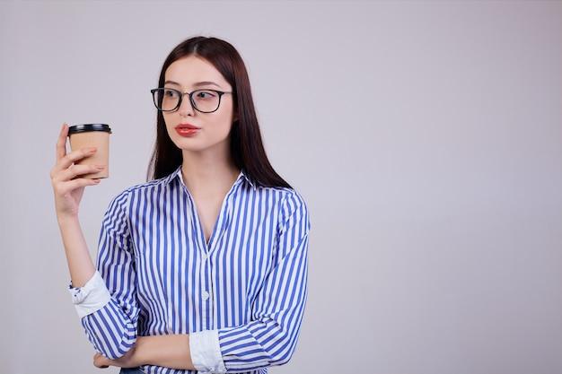 Frau in einem gestreiften hemd und einer schwarzen pc-brille steht mit einer braunen tasse kaffee in der hand auf grau. die frau schaut ruhig zur seite