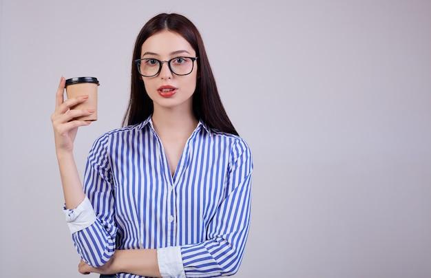 Frau in einem gestreiften hemd und in einer schwarzen pc-brille steht mit einem tasse kaffee in ihrer hand auf grau.
