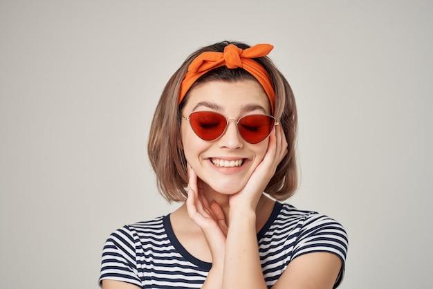 Frau in einem gestreiften t-shirt mit sonnenbrille mit einem verband auf dem kopf heller hintergrund