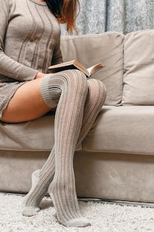 Frau in einem gestrickten pullover und in strümpfen, die ein buch lesen