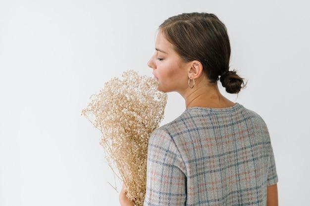 Frau in einem grau karierten kleid mit einem strauß trockenblumen