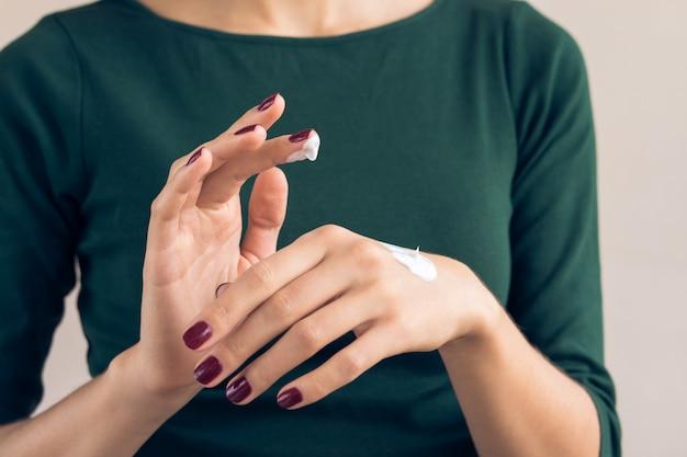 Frau in einem grünen t-shirt und in einer kastanienbraunen maniküre, die handcreme aufträgt