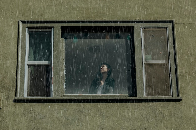Frau in einem haus an einem regnerischen tag