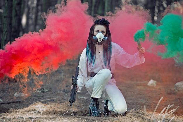 Frau in einem hazmat-anzug, der eine atemschutzmaske mit dreadlocks im wald mit rauchbomben trägt. konzept der strahlenverschmutzung und der nuklearen katastrophe.