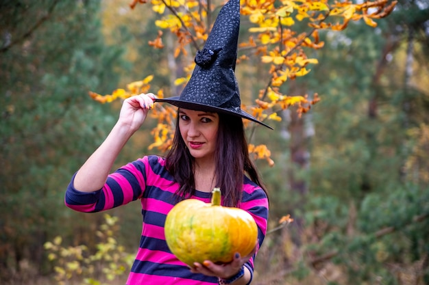 Frau in einem hexenkostüm mit einem kürbis im waldhintergrund glücklicher halloween-feiertag