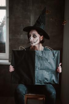 Frau in einem hexenkostüm und skelett make-up öffnet ein schwarzes zauberbuch für eine hexe an halloween.