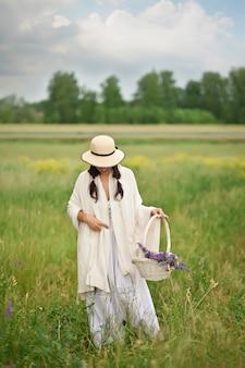 Frau in einem hut, der lila blumen in einem weidenkorb auf der wiese pflückt.