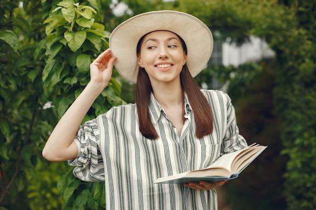 Frau in einem hut mit einem buch in einem garten