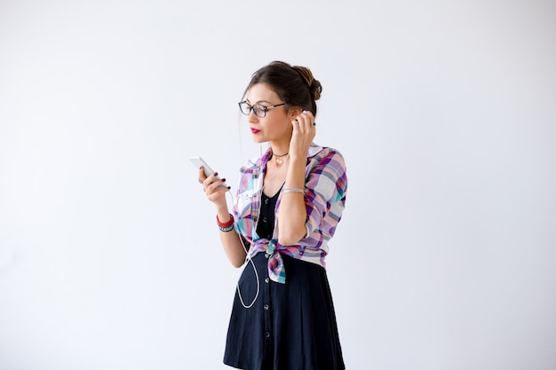 Frau in einem karierten hemd in den gläsern, die mit kopfhörern plaing sind