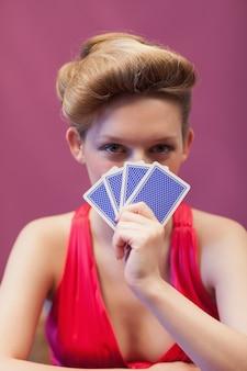 Frau in einem kasino, das karten vor gesicht hält